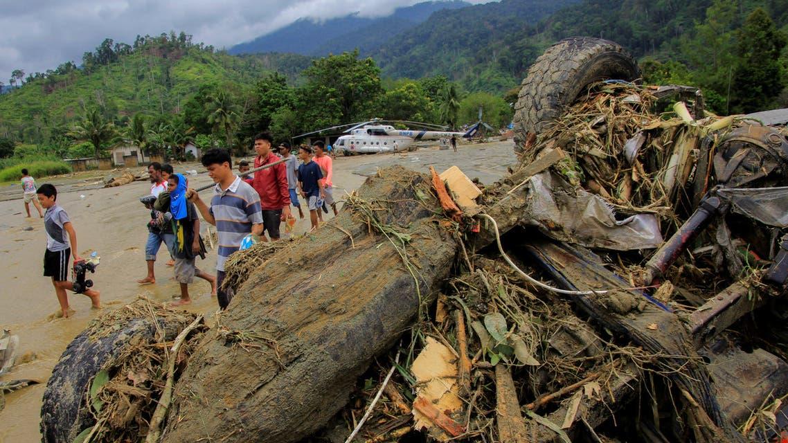أشخاص يسيرون بجوار سيارة مدمرة بفعل السيول في إقليم بابوا الإندونيسي