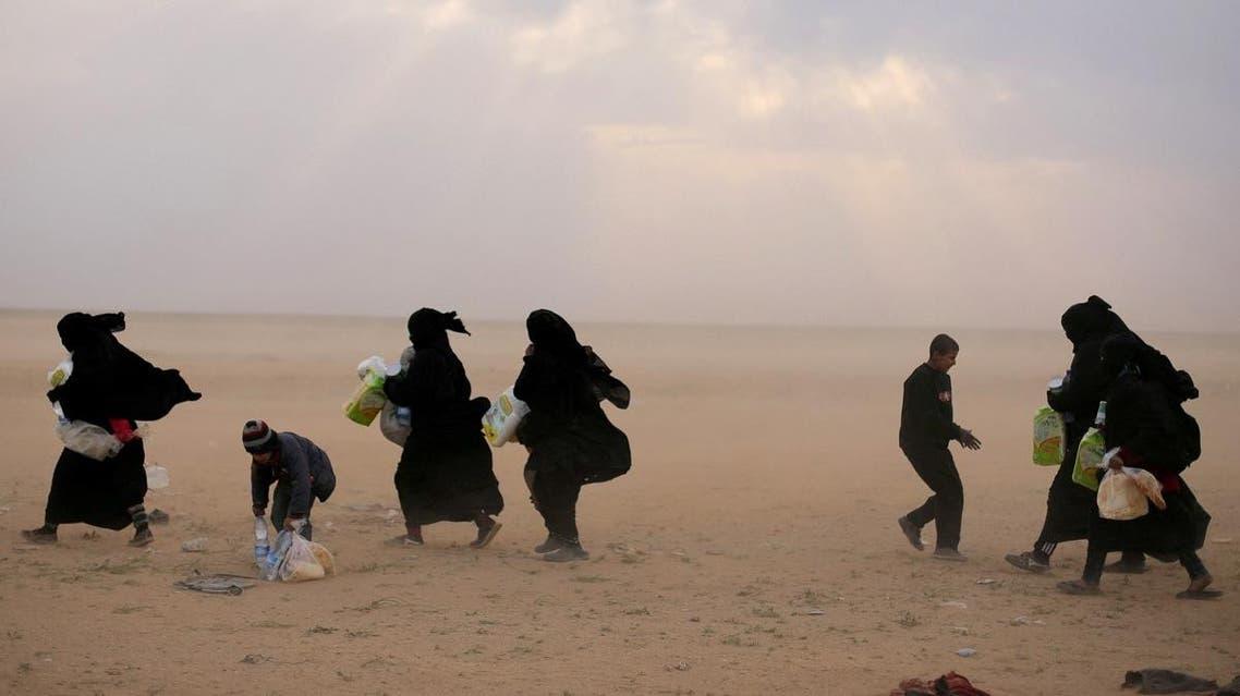 Women walk with their belongings near the village of Baghouz, Deir Al Zor province. (Reuters)