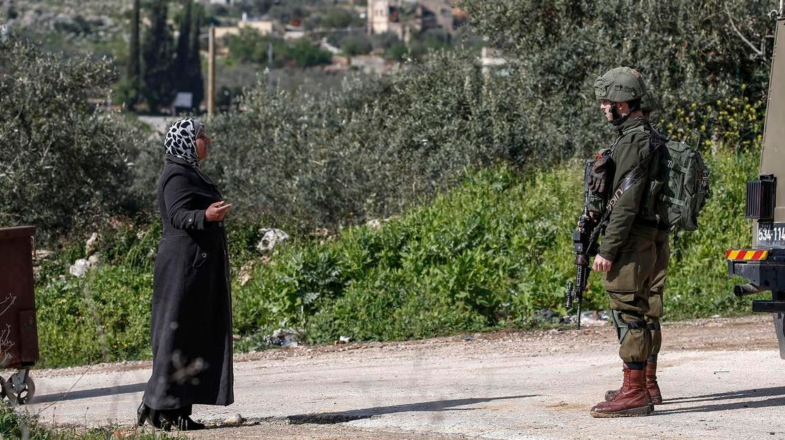 A Palestinian woman speaks with an Israeli soldier at a checkpoint as she tries to enter the village of Bruqin, near Nablus in the occupied West Bank on March 17, 2019, following the attack. (AFP)
