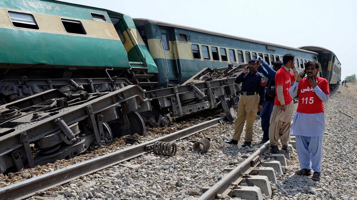 A police officer and rescue workers stand near to a derailed passenger train, after a bomb went off on track in Naseerabad. (Reuters)
