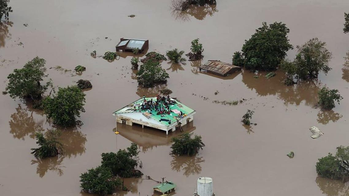 people on a roof surrounded by flooding in an area affected by Cyclone Idai in Beira, Mozambique. (AFP)