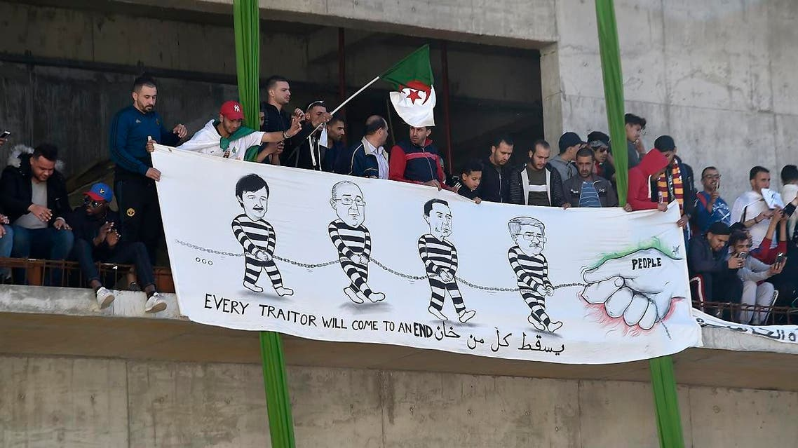 Algerians display a banner showing a farce of (from L) Said Bouteflika, Abdelmadjid Sidi Said, General Secretary of the General Union of Algerian Workers (UGTA), Algeria's Forum des chefs d'entreprises (FCE) chairman Ali Haddad, and Algerian former Prime Minister Ahmed Ouyahia in chain, as they demonstrate during the first Friday rally since the president's surprise announcement this week that he would not seek re-election. (AFP)