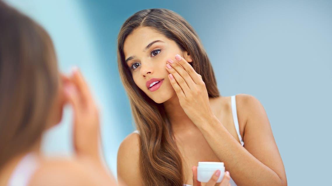 Patting on some obligatory moisturizer - Stock image