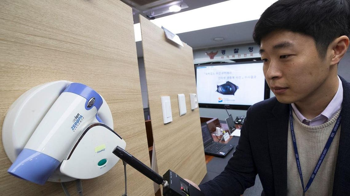 A police official testing a detector in front of a hidden mini-camera installed in a hair-dryer holder. (AFP)