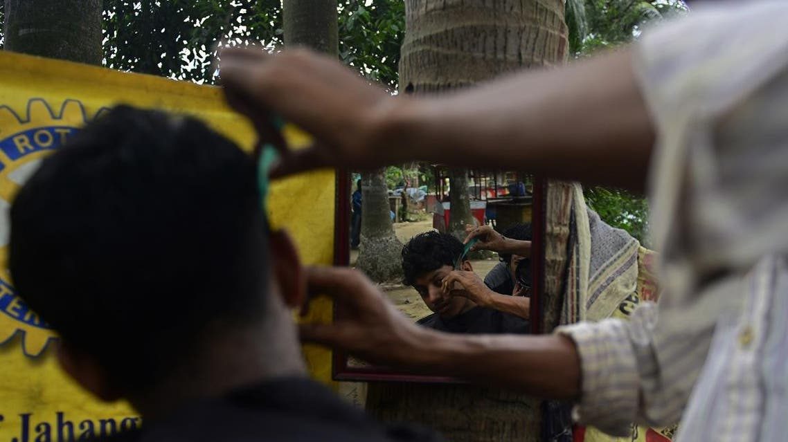 A Bangladeshi barber attends to a customer at his roadside stall in Dhaka. (AFP)