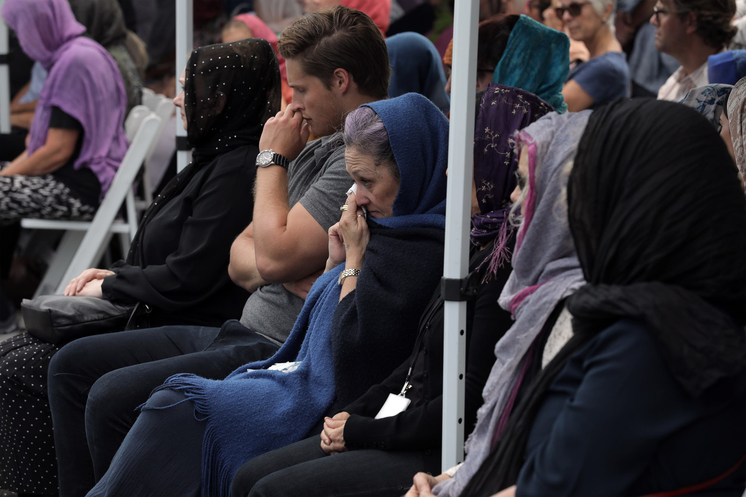 Local residents with head scarfs gather for the call to prayer and the moment of silence at Masjid Umar mosque (AFP)