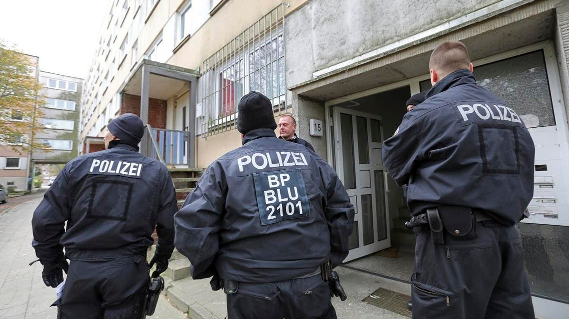 Police stand in front of a building in the northeastern German city of Schwerin (AP)