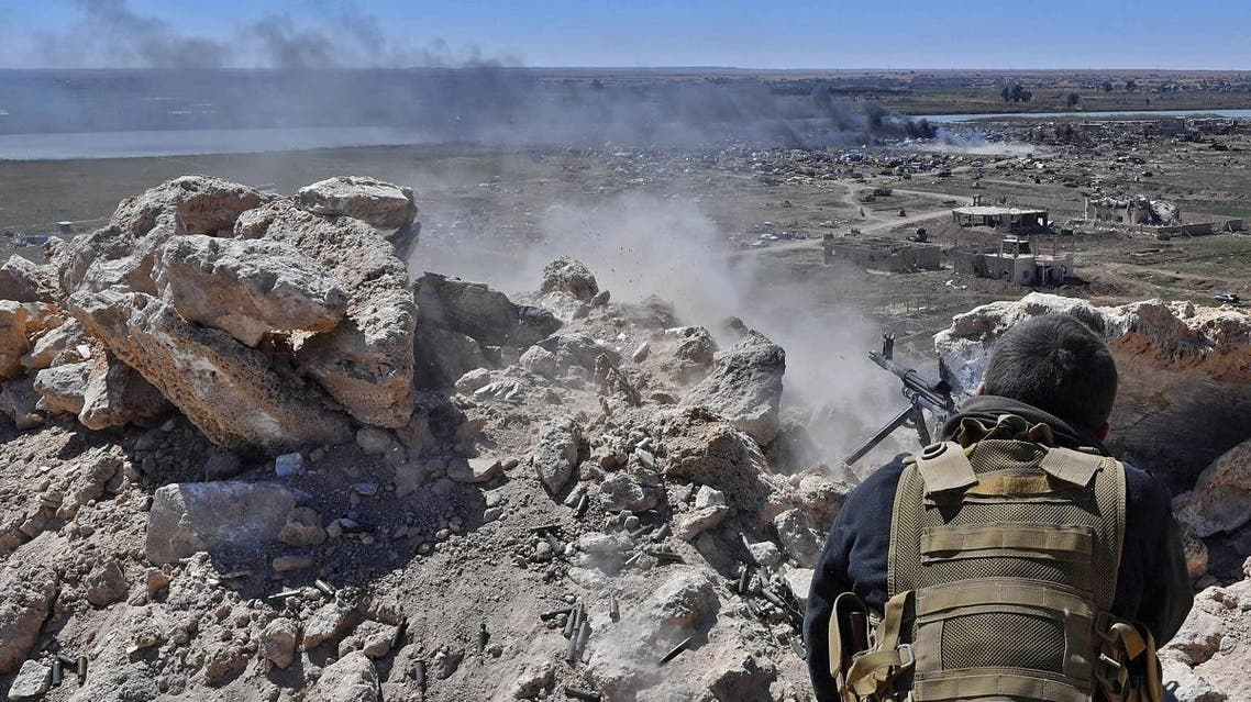 A fighter with the Syrian Democratic Forces (SDF) opens fire toward a part of Baghouz where remaining Islamic State (IS) group fighters are holding out in their last position, in the countryside of the eastern Syrian province of Deir Ezzor on March 18, 2019. (AFP)