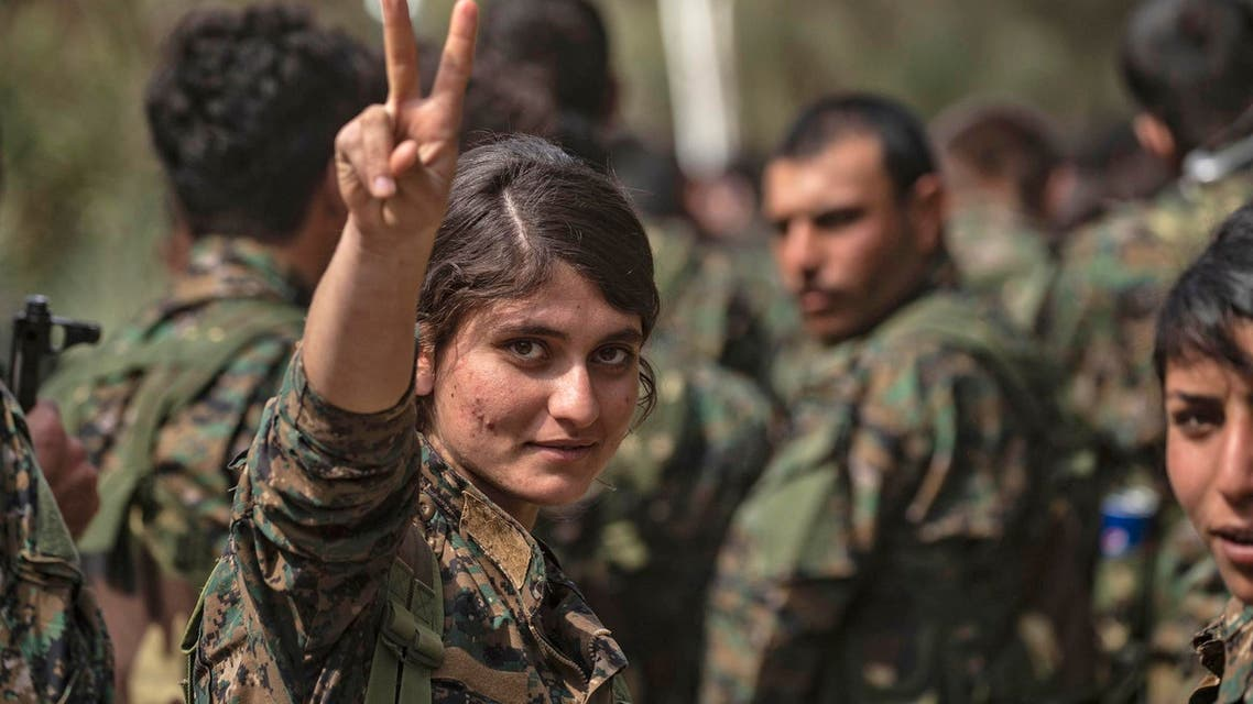 A female fighter of the Syrian Democratic Forces flashes the victory gesture while celebrating ISIS's defeat in the eastern Syrian Deir Ezzor province on March 23, 2019. (AFP)