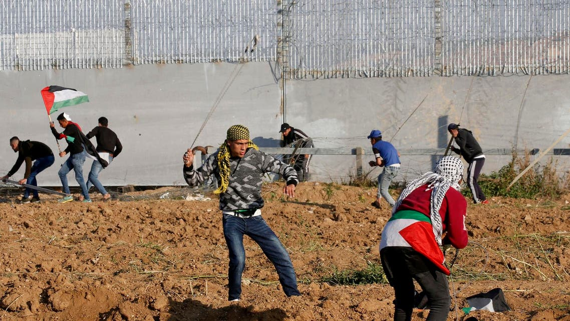 Palestinian protesters use slingshots to hurl objects during clashes with Israeli forces across the fence east of Gaza City on March 22, 2019. (AFP)
