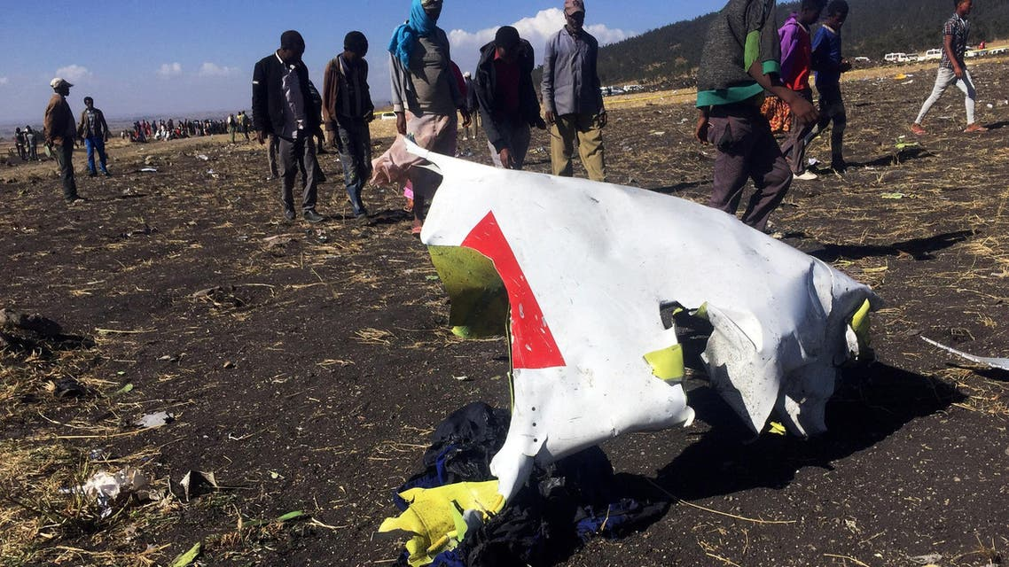 FILE PHOTO: People walk past a part of the wreckage at the scene of the Ethiopian Airlines Flight ET 302 plane crash, near the town of Bishoftu, southeast of Addis Ababa, Ethiopia March 10, 2019. REUTERS/Tiksa Negeri/File Photo