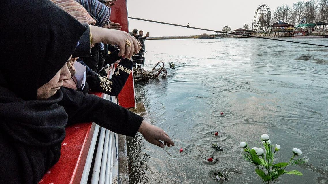 Iraqi women cast flowers into the Tigris river in remembrance of the victims of the capsized ferry in the northern Iraqi city of Mosul on March 22, 2019. (AFP)