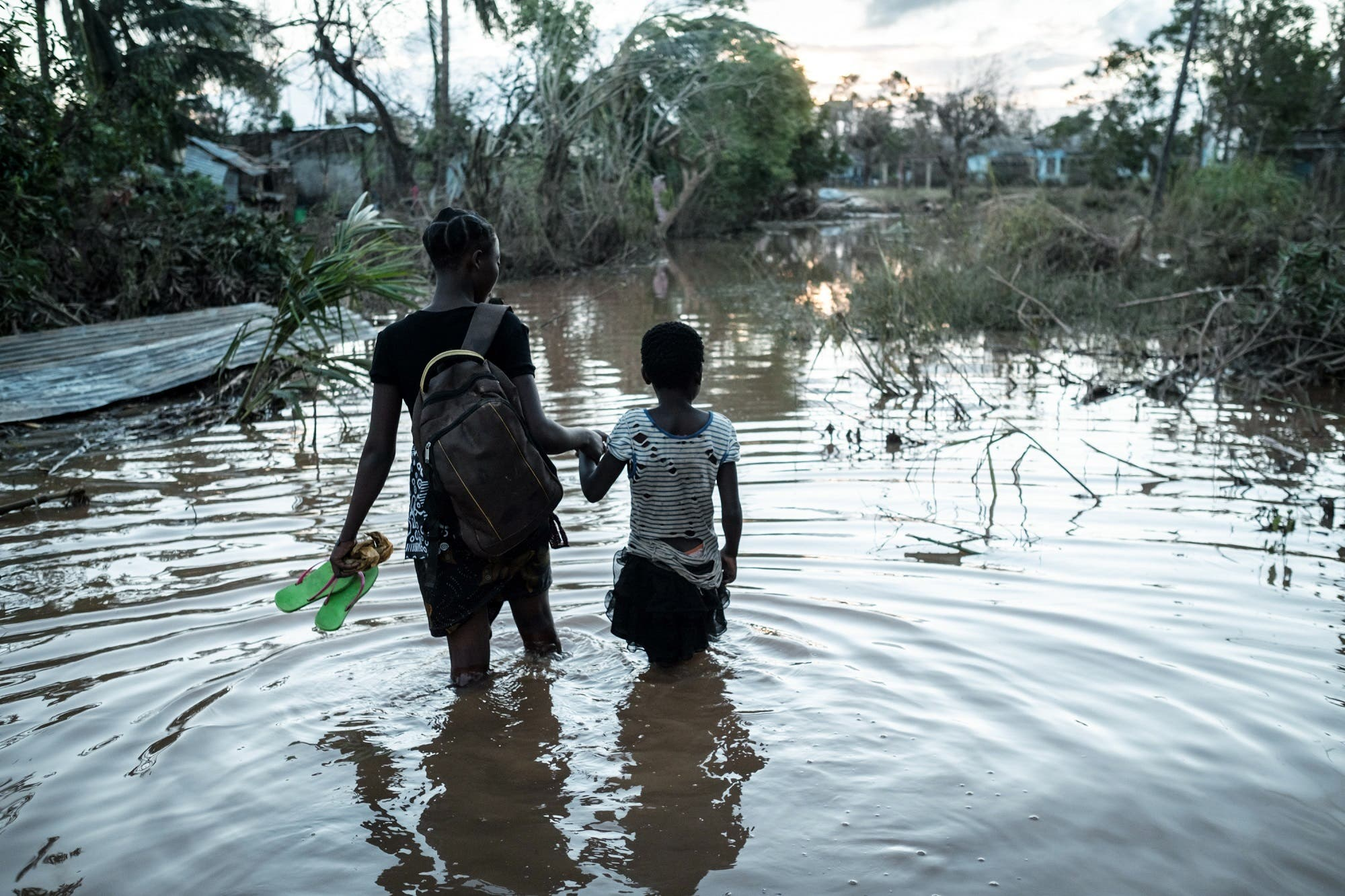 Rosita Moises Zacarias and her sister Joaninha Manuel walk in flooded waters from their house destroyed by the cyclone Idai, on March 22, 2019. (AFP)