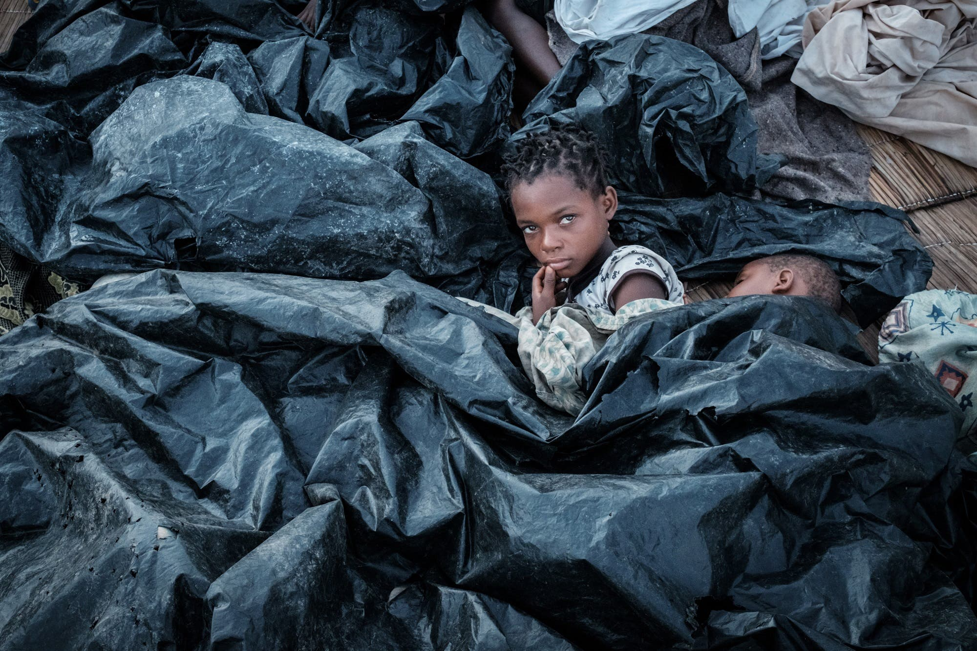 Enia Joaquin Luis, 11, wakes up under plastic sheets to protect herself from rain as she stays in shelter at the stands of Ring ground in Buzi, Mozambique, on March 23, 2019. (AFP)
