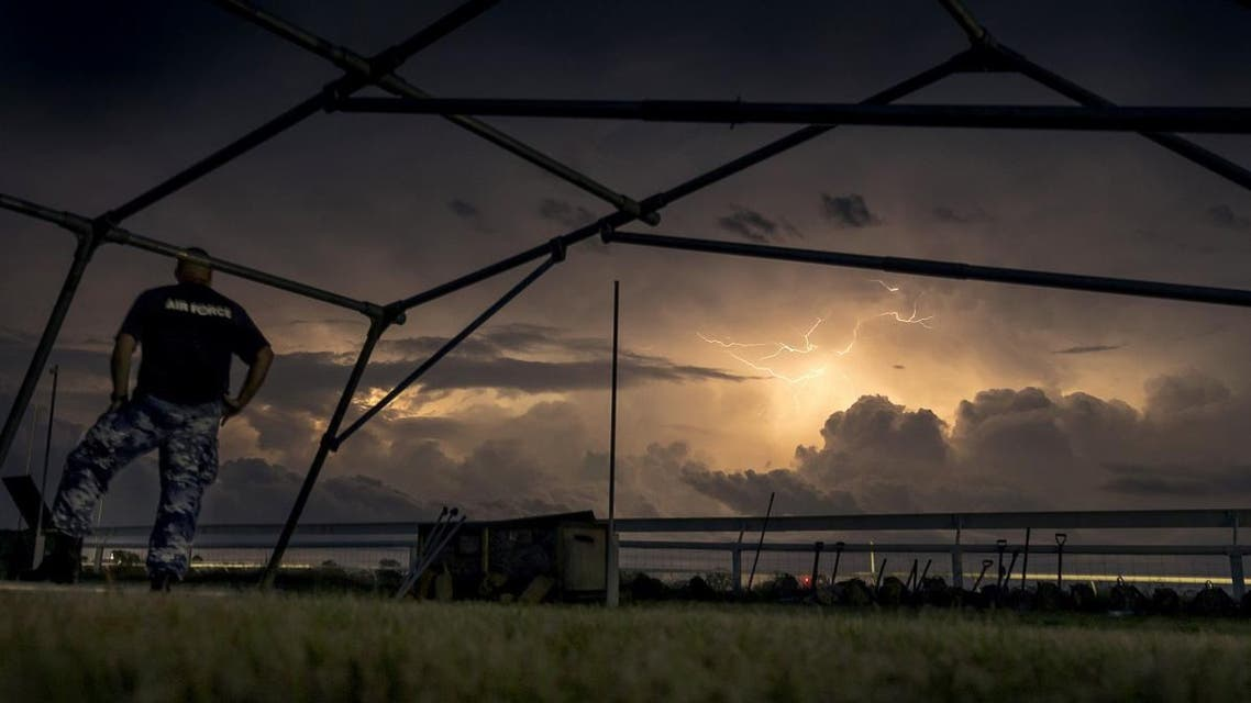 In this handout photo from the Commonwealth of Australia, Department of Defence taken on March 23, 2019 shows lightning in the skies surrounding Katherine Showgrounds as Australian Army soldiers from The 5th Battalion, Royal Australian Regiment and Royal Australian Air Force Base Tindal personnel set up emergency shelter tents for residents in anticipation of Tropical Cyclone Trevor. A severe category 3 cyclone blew into the key mining region of Pilbara in Western Australia on March 24, 2019, forcing evacuations and a halt to port operations, as the north of the country dealt with the effects of Cyclone Trevor, as the powerful category 4, weakened to a tropical storm overnight as it moved inland in the sparsely populated region. CPL TRISTAN KENNEDY / Commonwealth of Australia, Depar / AFP