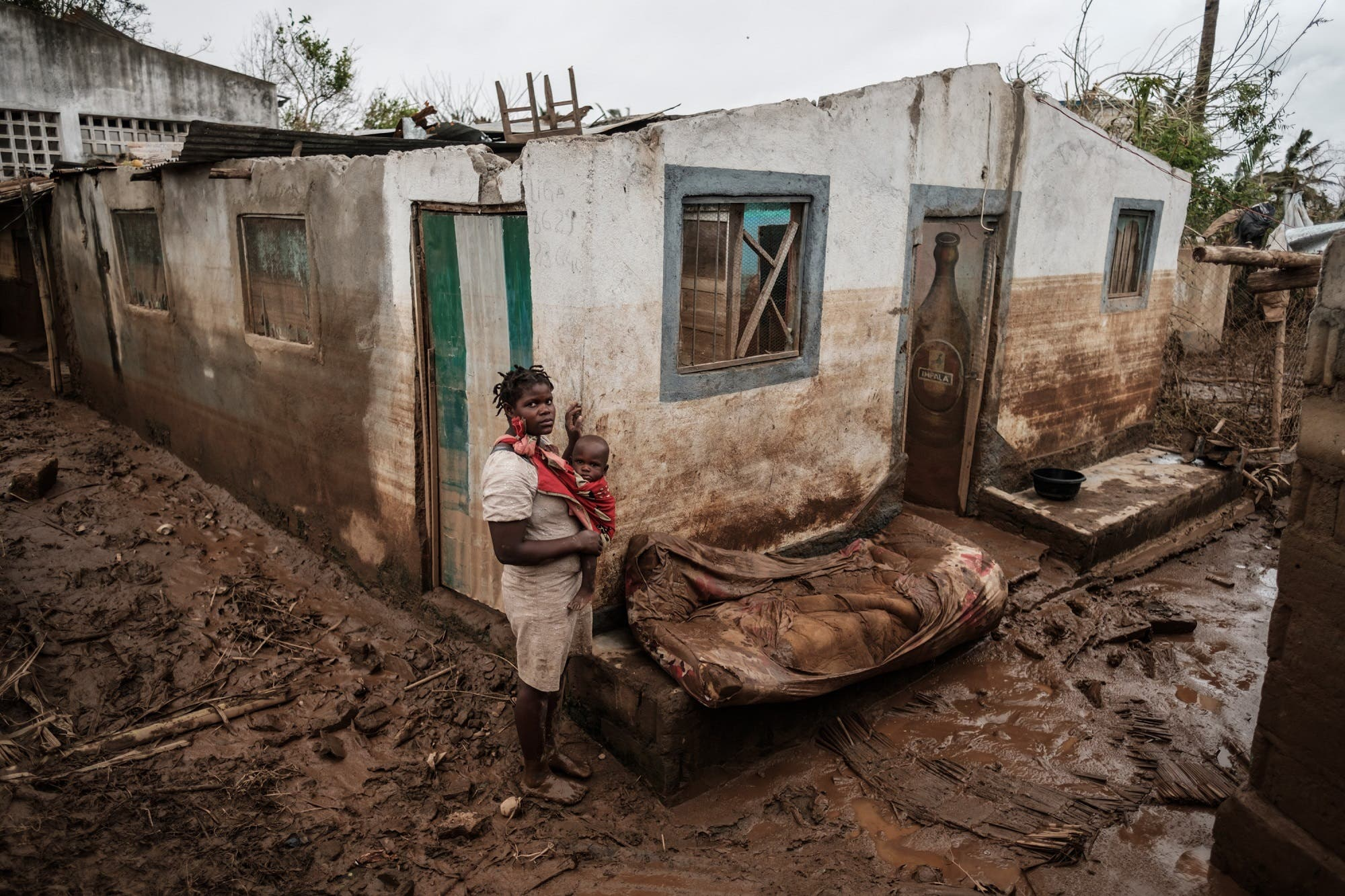 Rosa Tomas, 27, poses with her one-year-old son Dionisio Eduardo, in front of their destroyed and mud-covered home in Buzi, Mozambique, on March 23, 2019. (AFP)