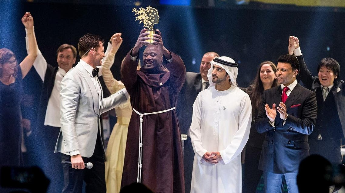 Kenyan teacher Peter Tabichi (C) holding up the Global Teacher Prize (GTP) trophy after winning the US$ 1 million award during an official ceremony in Dubai. (AFP)