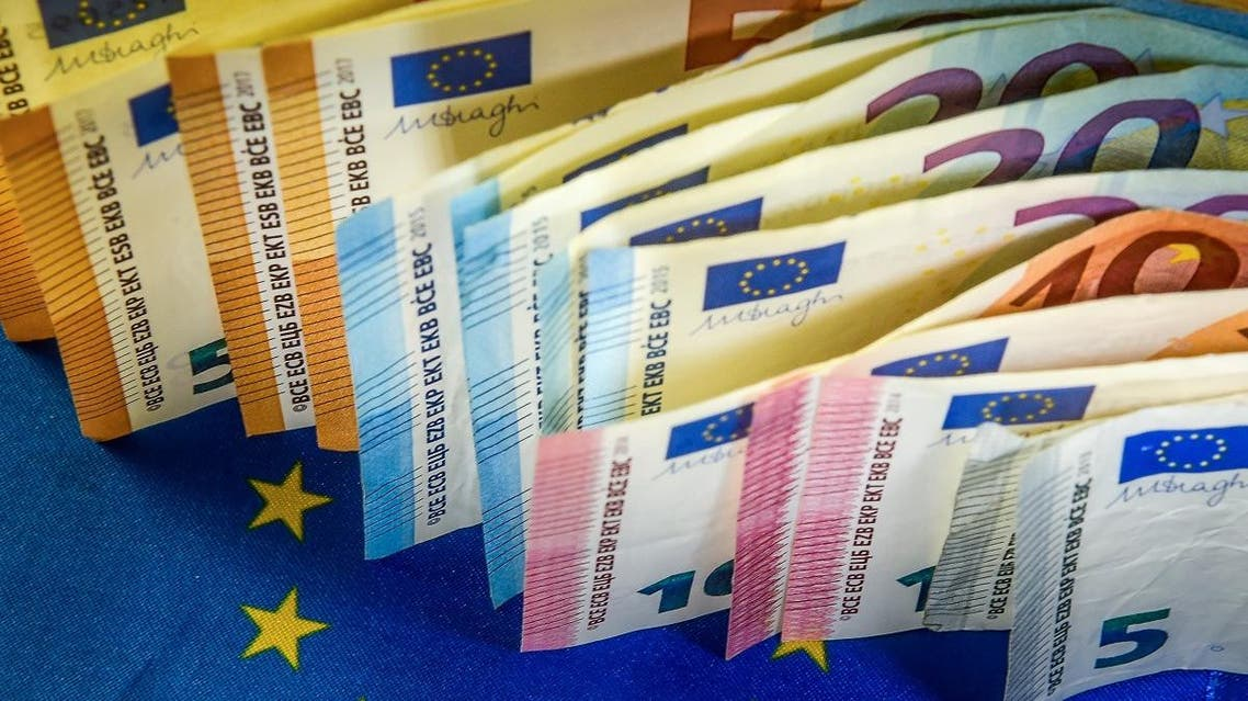 Euro banknotes are displayed next to a European Union flag. (AFP)