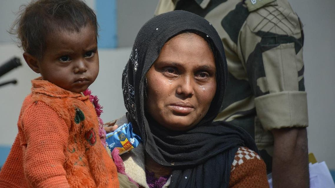 A Rohingya refugee weeps as she holds a child after they were detained while crossing the India-Bangladesh fenced border from Bangladesh, at Raimura village on the outskirts of Agartala, the capital of the northeastern state of Tripura, on January 22, 2019. Indian Border Security Force (BSF) officials said they had detained 31 Rohingya refugees crossing the border from Bangladesh.
