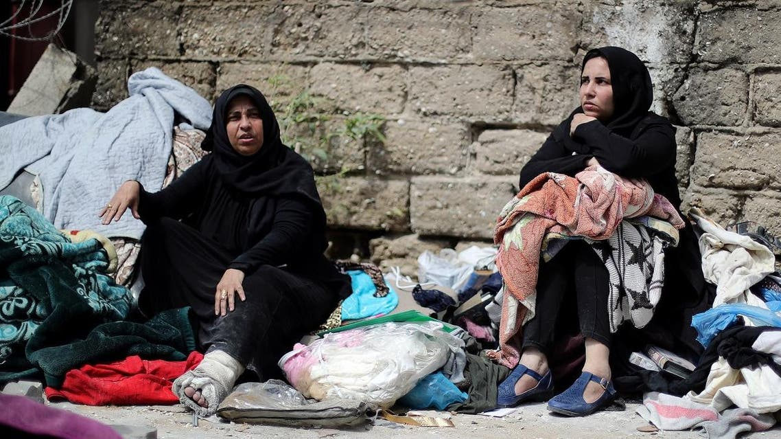 Palestinians sit with their belongings in a street outside their destroyed house in Gaza City. (Reuters)