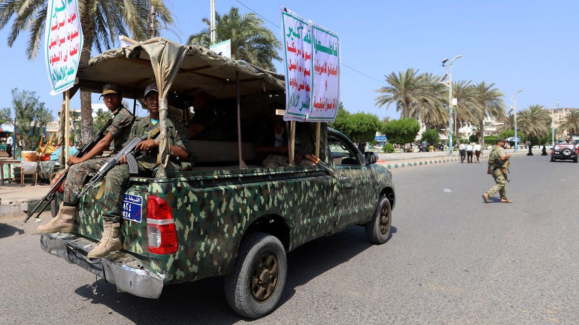 """Houthi militants ride on the back of a police patrol truck as they secure a street where Houthi supporters demonstrated against British Foreign Secretary Jeremy Hunt in Hodeidah, Yemen March 5, 2019. The placards read: """"Allah is the greatest .. death to America .. death to Israel .. a curse on Jews .. victory to Islam."""" and """"Boycott the American and Israeli goods!"""". REUTERS/Abduljabbar Zeyad"""