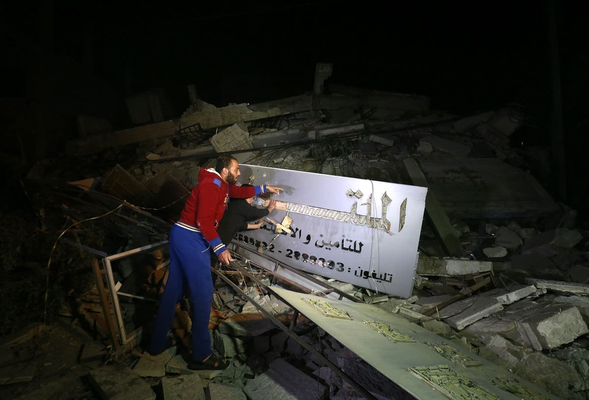 Palestinian men point at an insurance company sign amid the rubble of a building that collapsed from reported Israeli strikes in Gaza City. (AFP)
