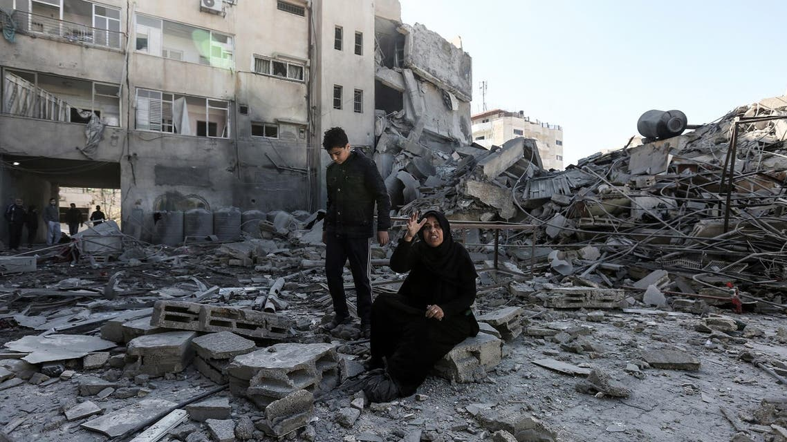 This March 26 picture shows a Palestinian woman sitting next to the rubble of a building after Israeli air strikes hit Gaza City sites.