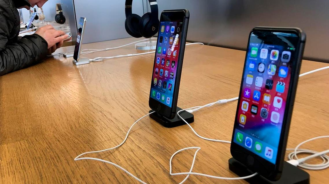 A man tries out a latest iPhone next to iPhone 8 and 8 Plus on display for sale at an Apple Store in Beijing, Tuesday, Dec. 11, 2018. (AP)