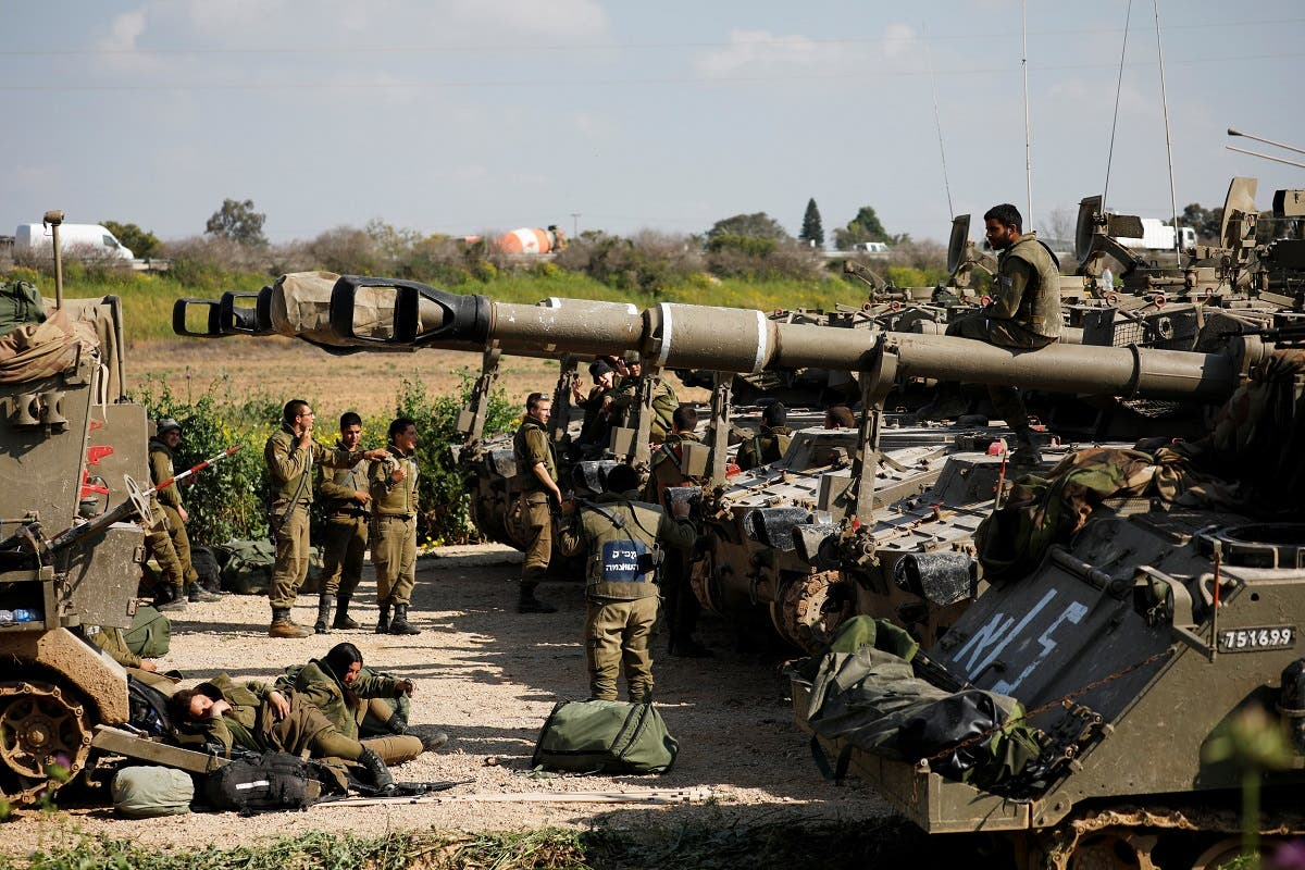 Israeli soldiers are seen next to mobile artillery units near the border with Gaza, in southern Israel, on March 27, 2019. (Reuters)