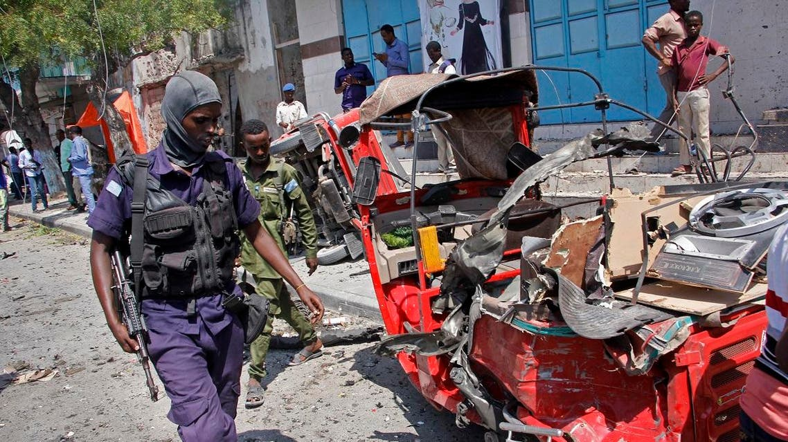 A policeman walks past a destroyed vehicle after an attack using an explosives-laden vehicle on a restaurant in Mogadishu, Somalia Thursday, March 28, 2019. (AP)