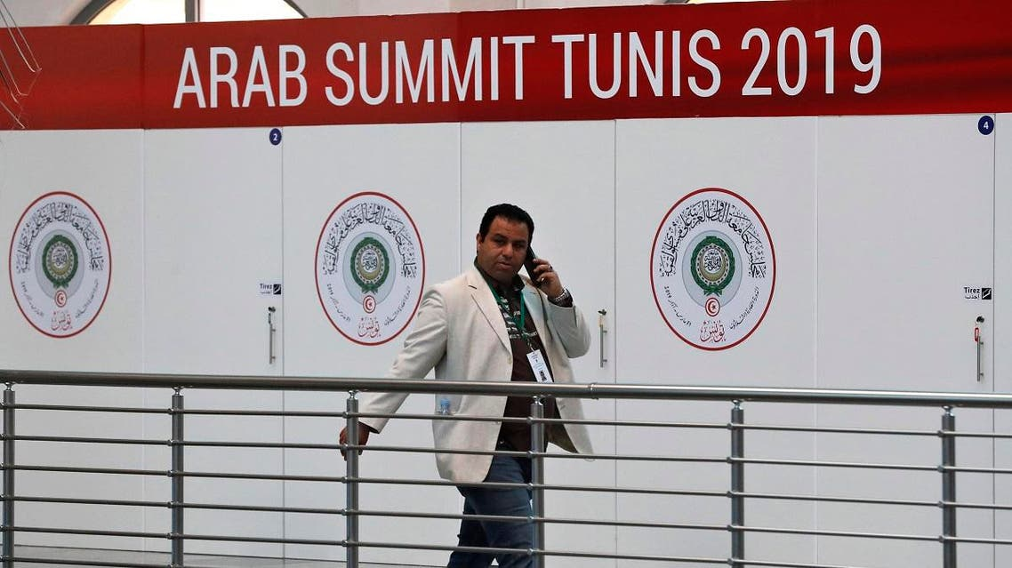 A Tunisian journalist walks in front the logo of the Arab League Summit, at the media center which will serve the journalists covering the summit, at the Culture City, in Tunis, Wednesday, March 27, 2019. (AP)