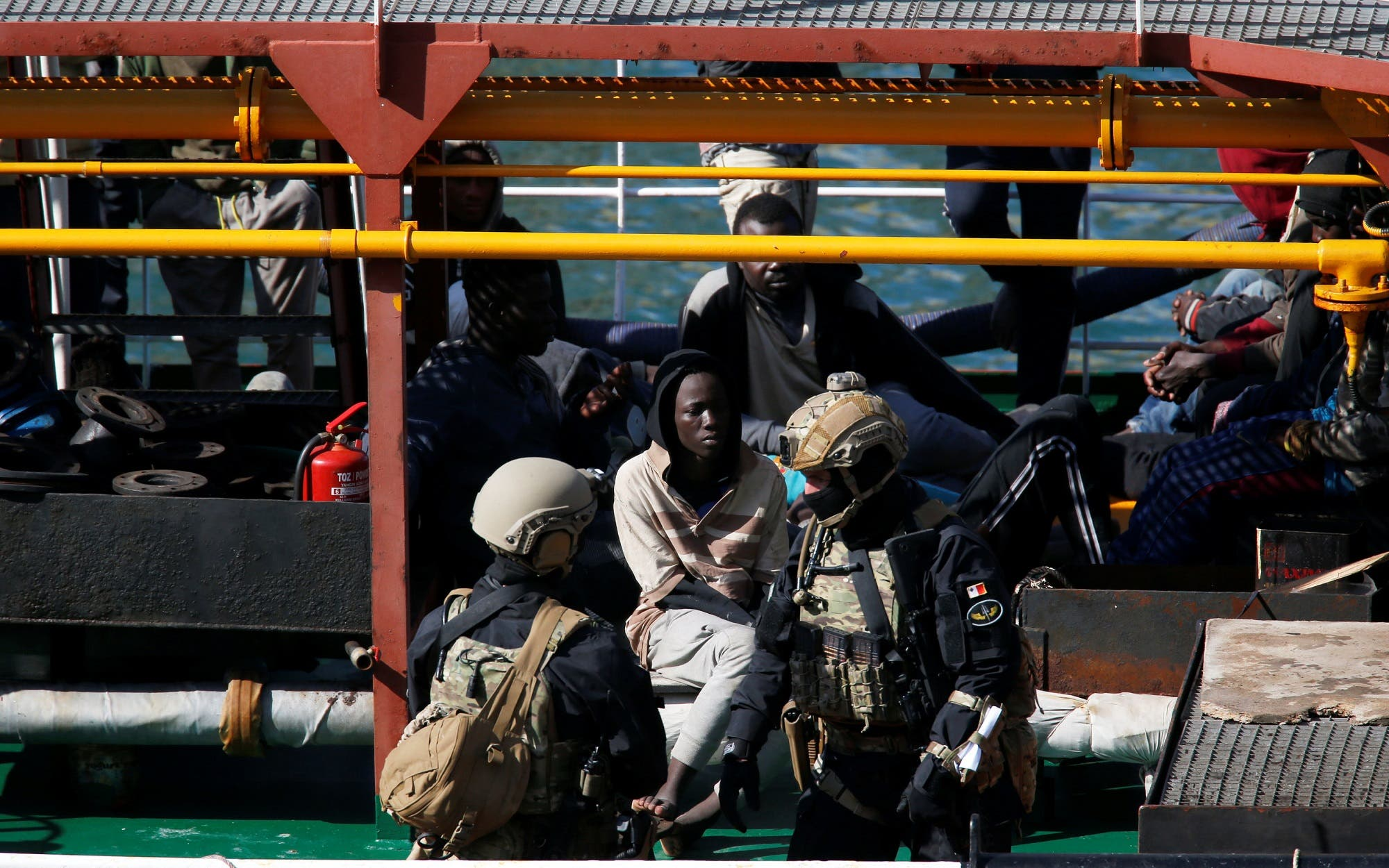 Maltese Special Forces soldiers guard a group of migrants on the merchant ship Elhiblu 1 after it arrived in Valletta's Grand Harbour, Malta on March 28, 2019. (Reuters)