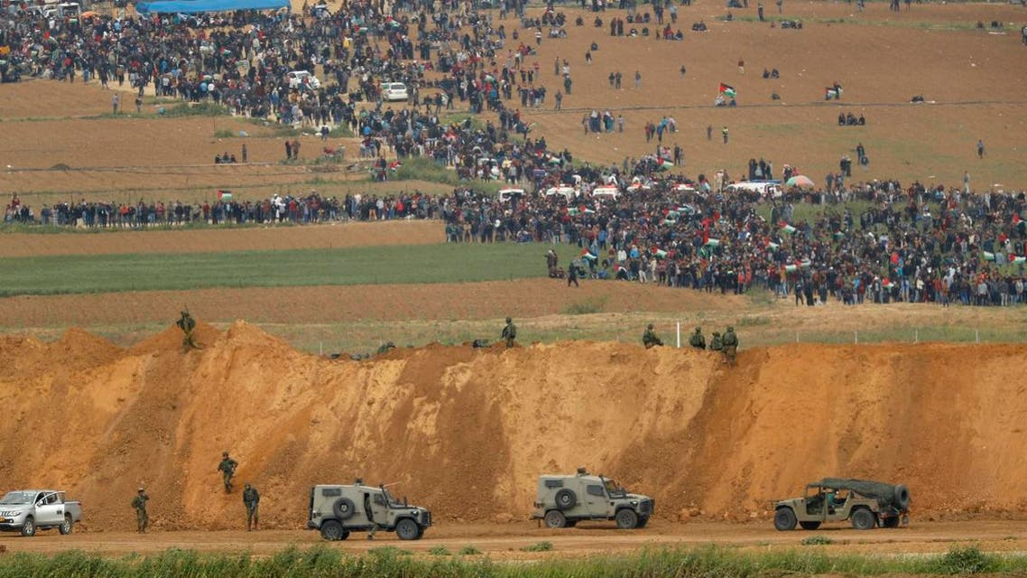 In this file photo taken on March 30, 2018 from the southern Israeli kibbutz of Nahal Oz across the border from the Gaza Strip, Palestinians participating in a tent city protest commemorating Land Day, with Israeli military vehicles seen below in the foreground. (AFP)