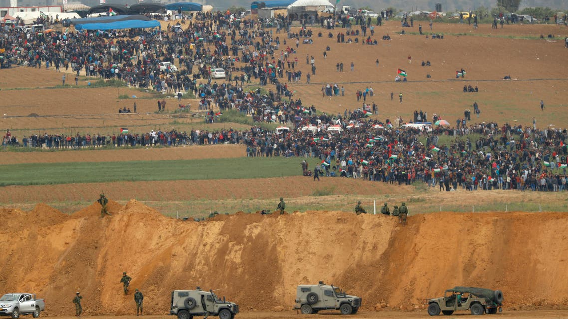 (FILES) In this file photo taken on March 30, 2018 from the southern Israeli kibbutz of Nahal Oz across the border from the Gaza Strip, Palestinians participating in a tent city protest commemorating Land Day, with Israeli military vehicles seen below in the foreground. A year after the start of protests, labelled the Great March of Return, and clashes on the Gaza-Israel border, more than 200 Palestinians have been killed by Israeli fire. More than 8,000 operations for other often serious but not life-threatening conditions -- such as gallstones or hip replacements -- have been postponed in Gaza hospitals according to the WHO. Explosive devices, stones and fireworks have been used against Israeli forces. There has been occasional gunfire, with one soldier killed by a Palestinian sniper.