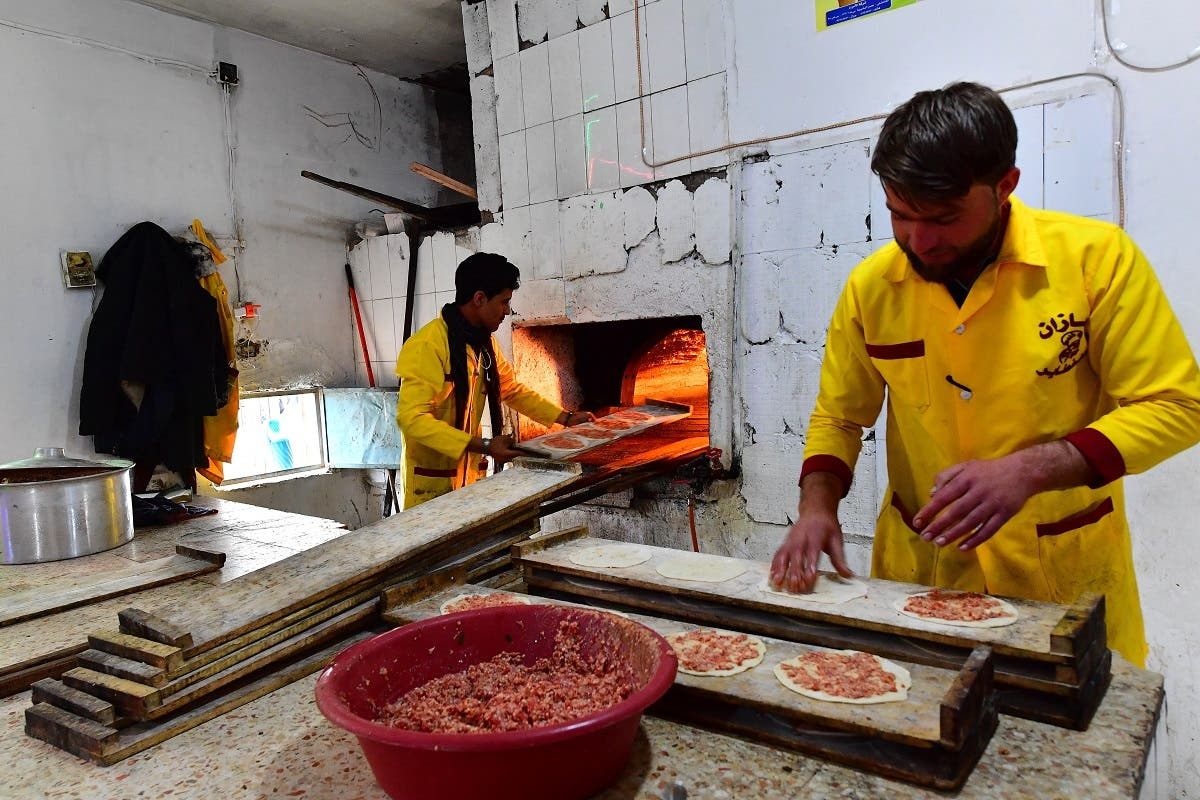 Bakers prepare local meat pies in the souk or market of al-Hol camp for displaced people in northeastern Syria. (AFP)