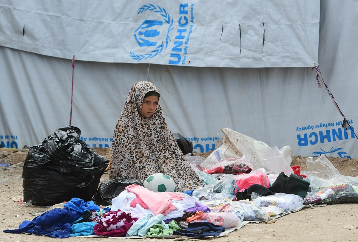 A displaced girl sells second-hand items in the souk or market of al-Hol camp for displaced people in northeastern Syria. (AFP)
