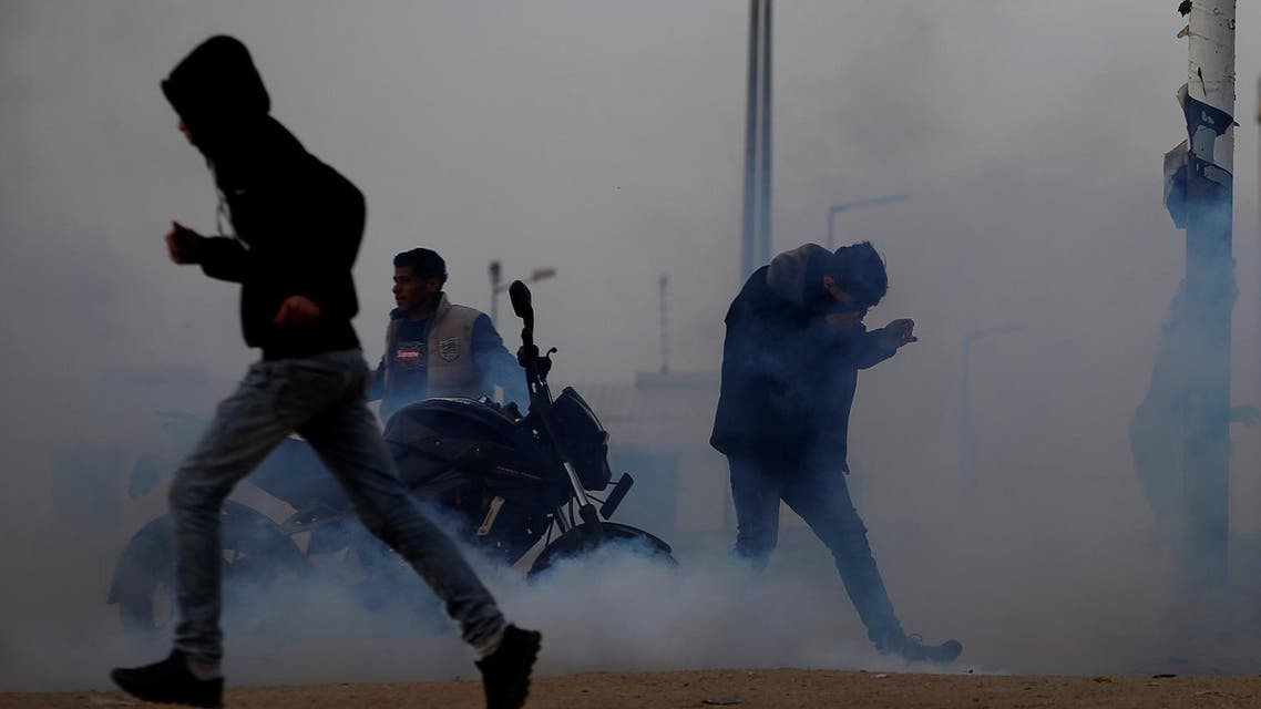 Palestinians react to tear gas fired by Israeli troops during a protest at the Israeli-Gaza border fence, on March 29, 2019. (Reuters)