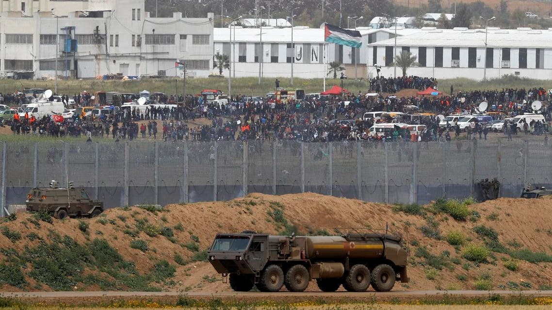 """Palestinian protesters demonstrating across the fence by the border with Israel as they mark the first anniversary of the """"March of Return"""" protests, with Israeli army vehicles seen in the foreground. (AFP)"""