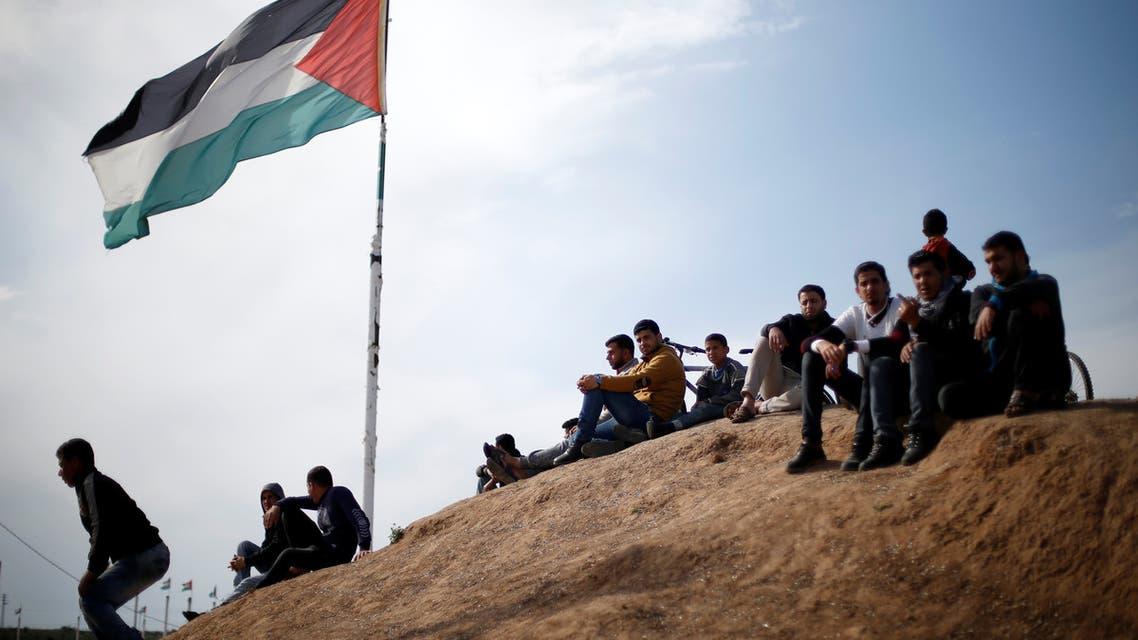 فلسطينيون يجلسون بالقرب من السياج الحدودي بين إسرائيل وغزة ، قبل الذكرى الأولى للاحتجاجات الحدودية ، شرق مدينة غزة