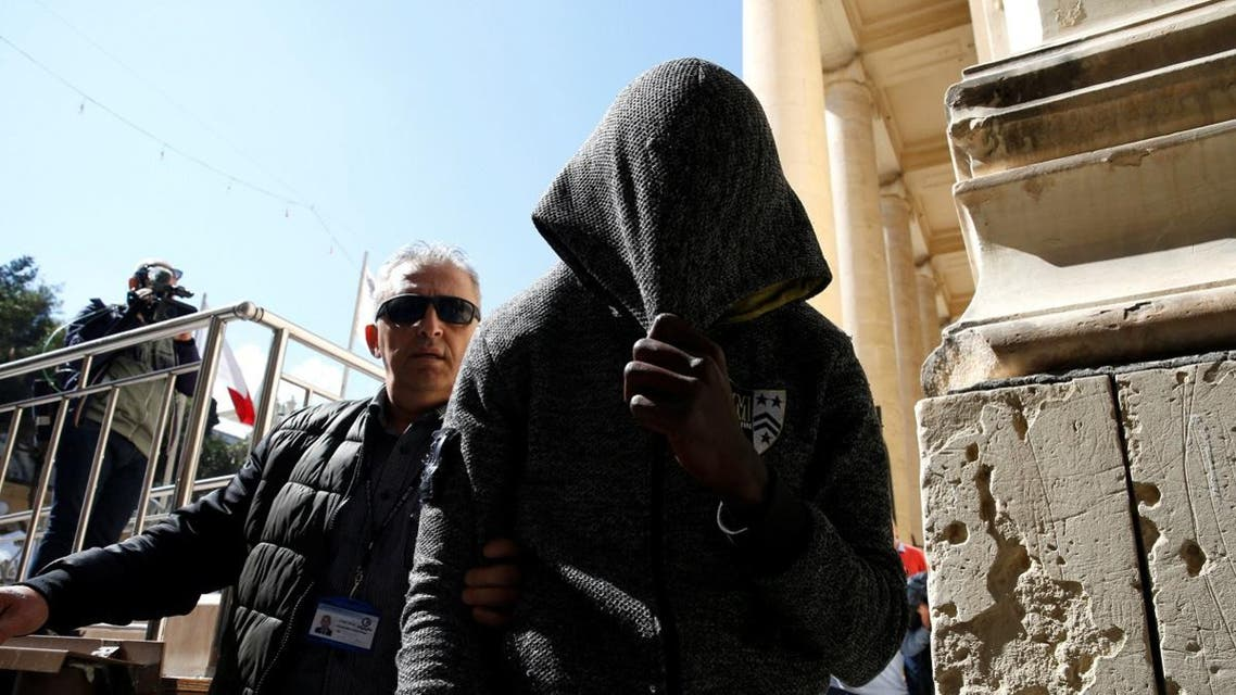 One of the migrants charged with hijacking the merchant ship Elhiblu 1 is escorted by a police officer out of the Courts of Justice in Valletta. (Reuters)