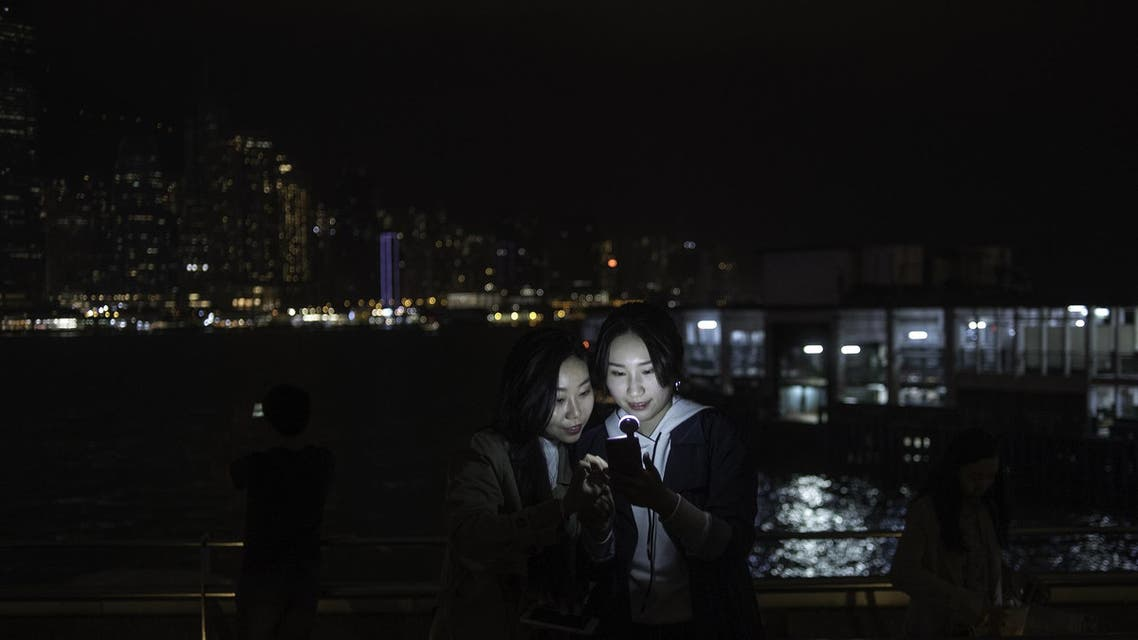 Two women look at a mobile phone after the skyline buildings lights were switched off for Earth Hour in Hong Kong on March 24, 2018. (AFP)