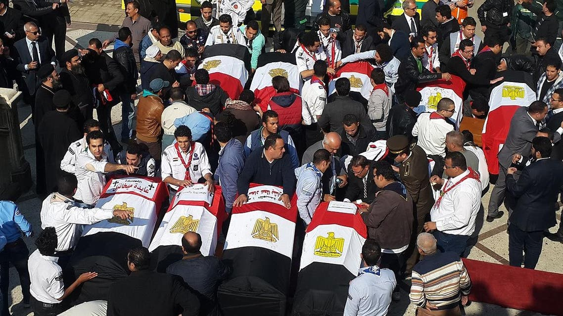A file photo showing Egyptian mourners and officials stand next to the coffins of victims of a terror attack that targeted a Coptic Orthodox Church. (AFP)