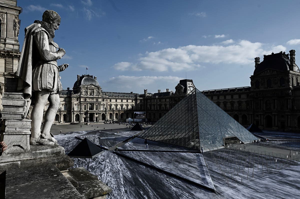 The Louvre pyramid is seen during preparations of the installation of French contemporary artist and photographer Jean Rene, aka JR, in the main courtyard of the Louvre Museum in Paris on March 29, 2019. (AFP)