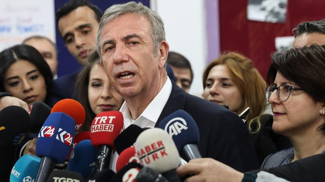 Mansur Yavas (C) speaks to the press, next to his wife Nursen Yavas (R), at a polling station during the local elections in Ankara, on March 31, 2019. (AFP)