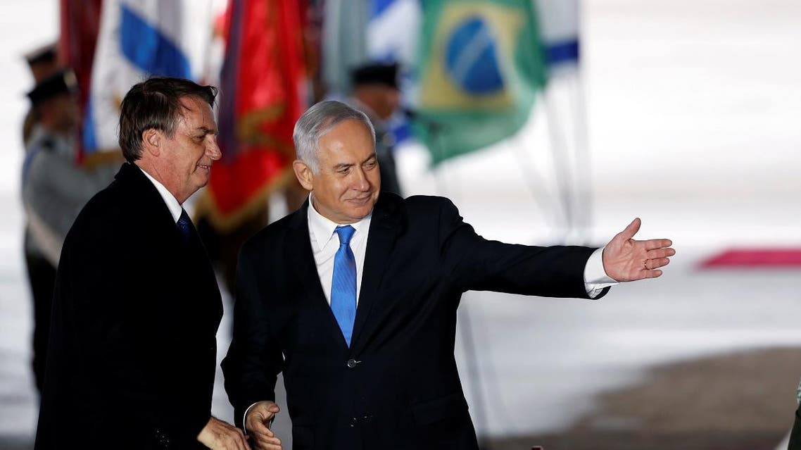 Israeli Prime Minister Benjamin Netanyahu gestures as he stands next to Brazilian President Jair Bolsonaro during a welcoming ceremony upon his arrival in Israel, at Ben Gurion International airport in Lod, near Tel Aviv, Israel. (Reuters)