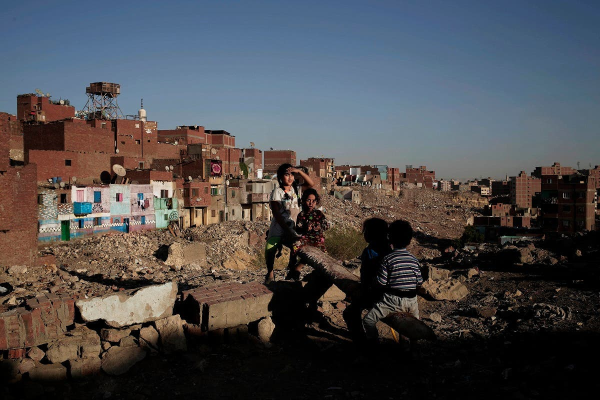 Children play on a makeshift see-saw made out of a tree trunk in slum area Ezbet Khairallah, Cairo, Egypt. (AP)