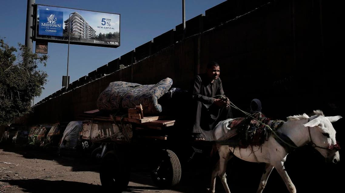 In this Oct. 28, 2018 photo, a man on a donkey cart makes his way under a residential billboard advertisement for a gated compound, near a wall that separates the ring road from slum area Ezbet Khairallah, in Cairo, Egypt. (AP)
