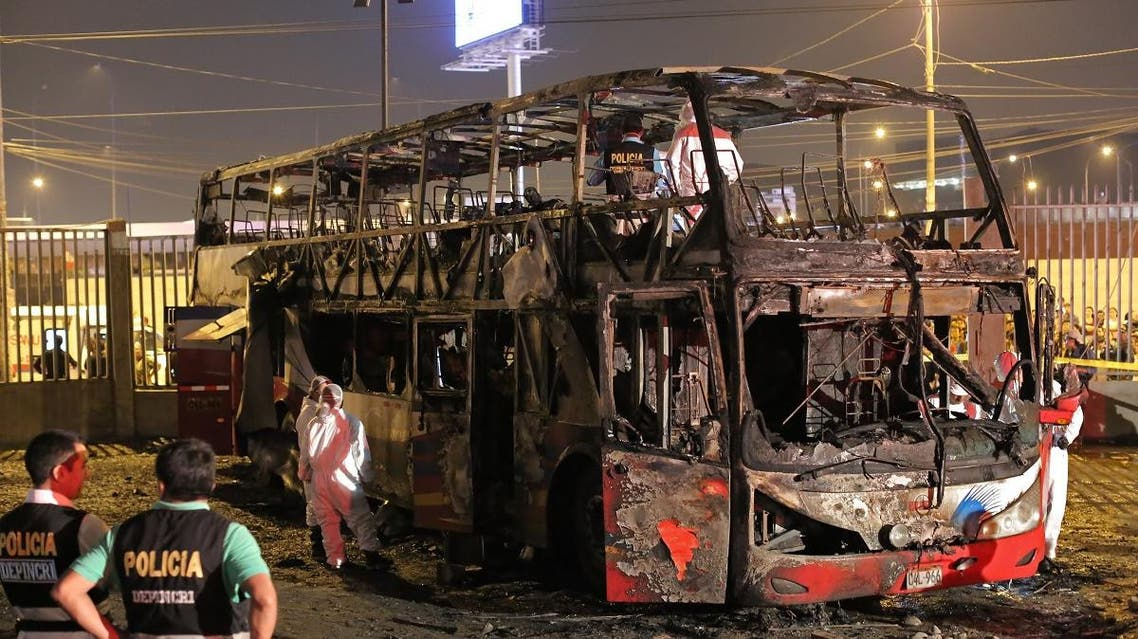 Police officers stand next to the remains of a bus that caught fire an interprovincial bus station in a populous district north of Lima and left 20 people dead on March 31, 2019. (AFP)