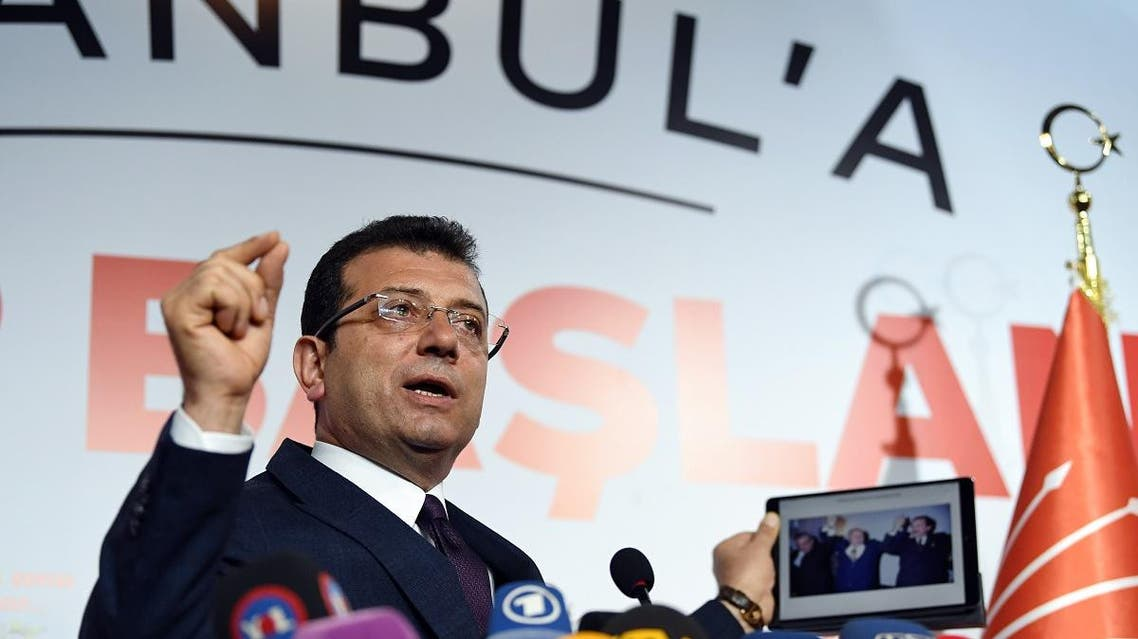 Ekrem Imamoglu, who claimed victory as Istanbul mayor, shows a picture of the 1994 local election featuring Istanbul Metropolitan municipality Refah Party (RP) candidate Recep Tayyip Erdogan (R), conservative Refah Party (RP) leader Necmettin Erbakan (C) and his opponent Social Democratic Populist Party (SHP) Nurettin Sozen, on his tablet during a press conference. (AFP)