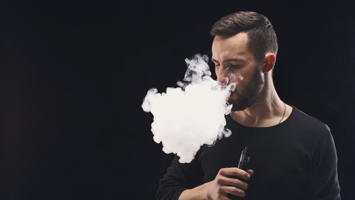 Young man vaping e-cigarette with smoke on black - Stock image